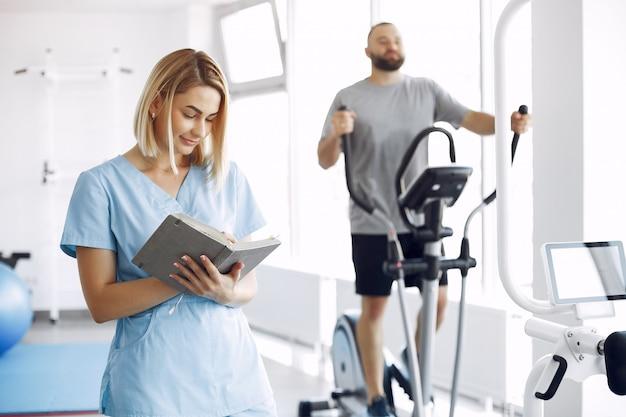 Paciente haciendo ejercicio en bicicleta de spinning en el gimnasio con el terapeuta