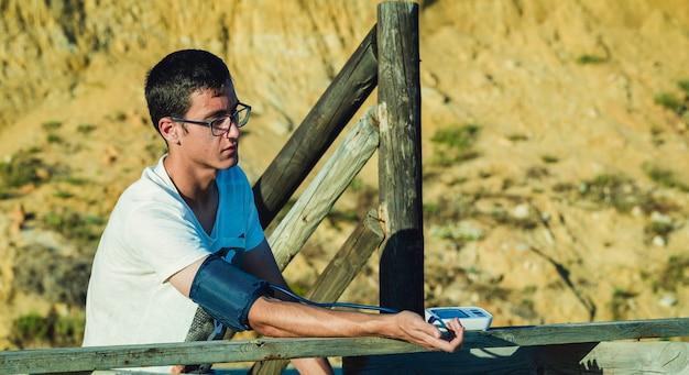 Paciente hipertenso realizando una prueba automática de presión arterial en el exterior.