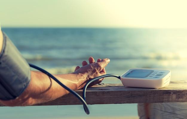 Paciente hipertenso realizando una prueba automática de presión arterial en la playa.