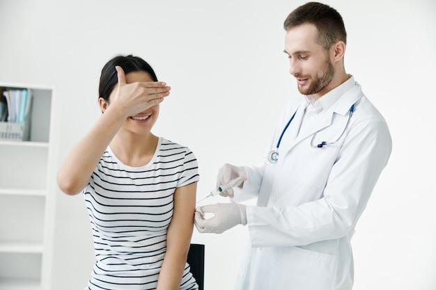 Paciente en un hospital se cubre la cara con una inyección en el hombro