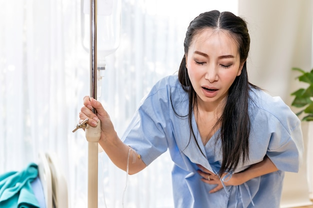 Paciente joven asiática caminando y dolor menstrual en la habitación del hospital.