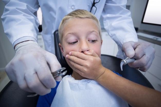 Paciente joven asustado durante un chequeo dental