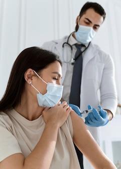 Paciente joven con máscara médica siendo vacunado por médico