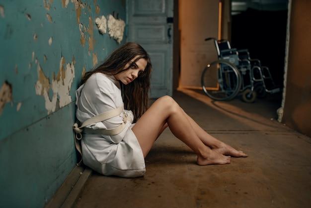 Paciente loco en camisa de fuerza sentado en el suelo