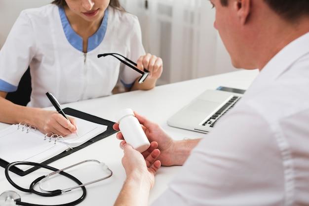 Paciente manos sosteniendo pastillas mientras el médico está escribiendo