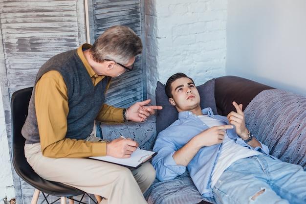 Paciente masculino infeliz escuchando el consejo de un consejero psicólogo