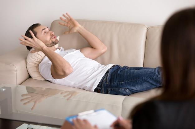 Paciente masculino joven que miente en el sofá que habla con el psicólogo de sexo femenino