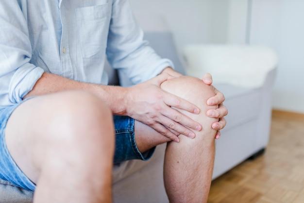 Paciente masculino maduro que sostiene la rodilla en dolor.