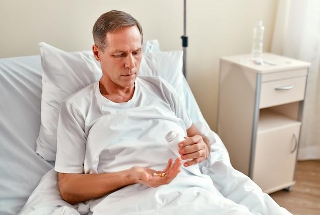 Un paciente masculino maduro está en rehabilitación en un hospital moderno y tiene un medicamento en la mano para poder tomarlo y recuperarse antes.