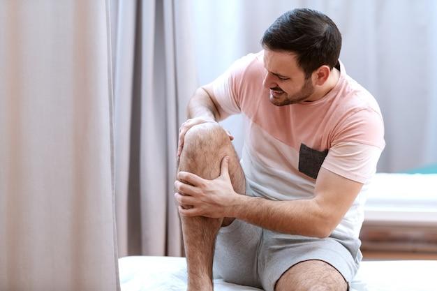 Paciente masculino de raza blanca sentado en la cama del hospital y sosteniendo la rodilla que se lesionó.