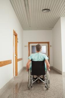 Paciente masculino sentado en una silla de ruedas en el pasillo