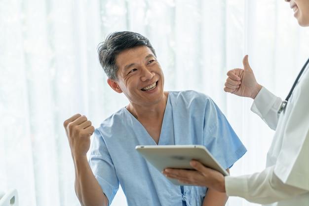 Paciente mayor asiático en cama de hospital discutiendo con doctora