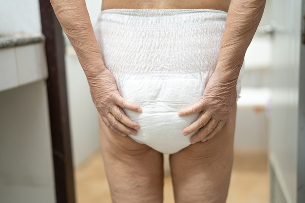 Paciente mayor asiático de la mujer que lleva el pañal de la incontinencia en el hospital.