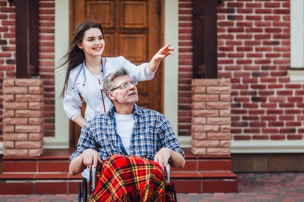 Paciente mayor contento con amable médico en el hogar de ancianos. tiempo juntos