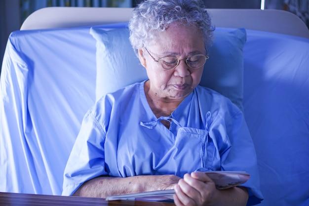 Paciente mayor o mayor asiático de la mujer de la señora mayor que lee un libro mientras que se sienta en cama en hosp