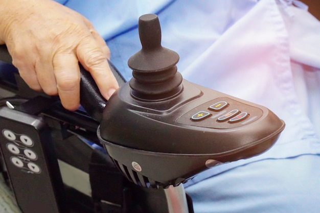Paciente mayor o mayor asiático de la mujer de la señora mayor en la silla de ruedas eléctrica