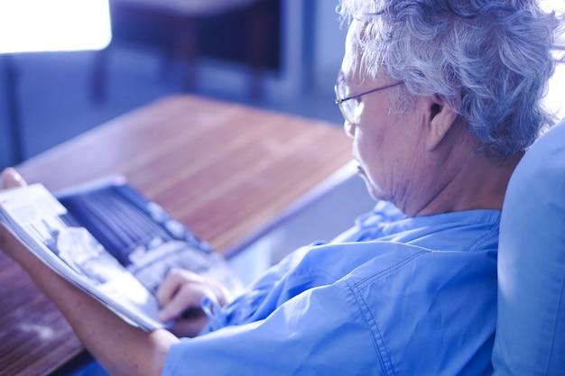 Paciente mayor o mayor asiático de la mujer de la señora que lee un libro mientras que se sienta en cama en el oficio de enfermera
