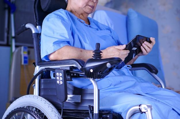 Paciente mayor o mayor asiático de la señora mayor mujer mayor que se sostiene en su tableta digital de las manos y que lee correos electrónicos mientras que se sienta en cama en sala de hospital de enfermería