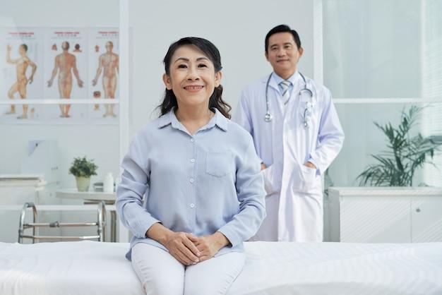 Paciente mayor sonriente que presenta para la fotografía
