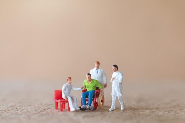 Paciente en miniatura en silla de ruedas consultando con médicos sobre fondo claro