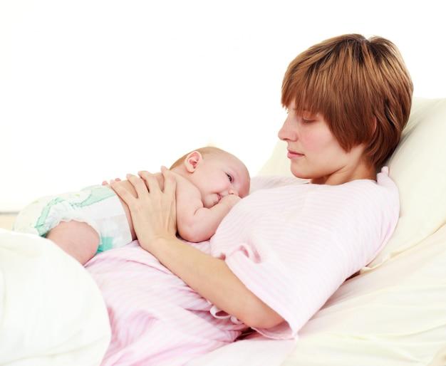 Paciente mirando a su bebé recién nacido en la cama