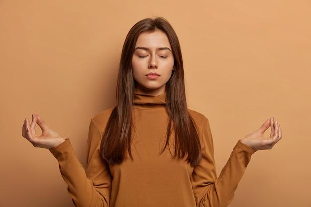 Paciente mujer aliviada hace un gesto de mudra, medita en interiores, intenta relajarse, respira profundamente y alcanza el nirvana