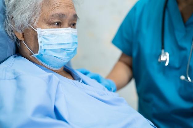 Paciente mujer asiática con protector facial para proteger la infección de seguridad coronavirus covid-19 virus en la sala del hospital de enfermería de cuarentena.