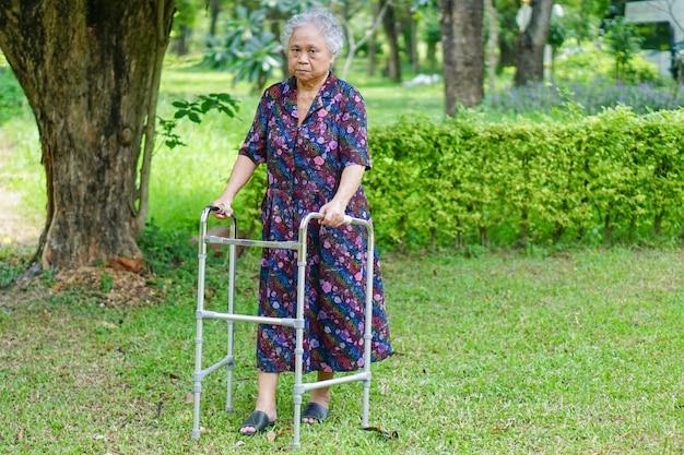 Paciente mujer asiática senior dama caminar con andador en el parque.