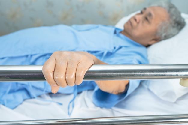 Paciente mujer mayor asiática acostarse manejar la cama de riel en el hospital.