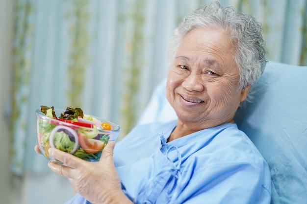Paciente mujer mayor asiática desayunando en el hospital.