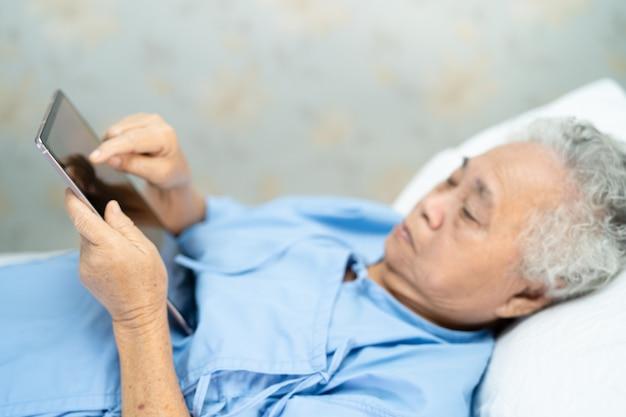 Paciente mujer mayor asiática que sostiene la tableta digital en el hospital.