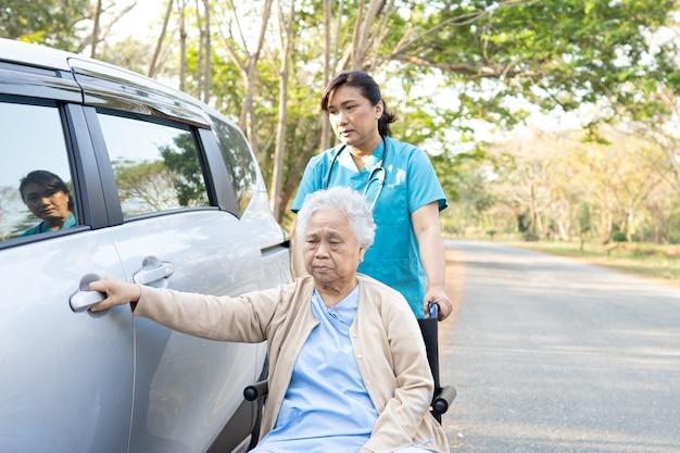 Paciente mujer mayor asiática sentada en silla de ruedas se prepara para llegar a su coche.