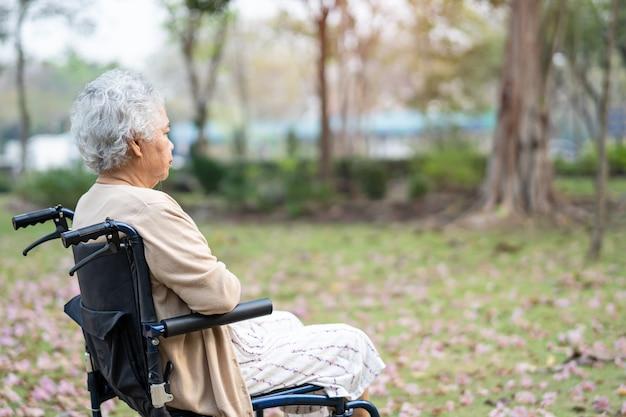 Paciente mujer mayor asiática en silla de ruedas en el parque.