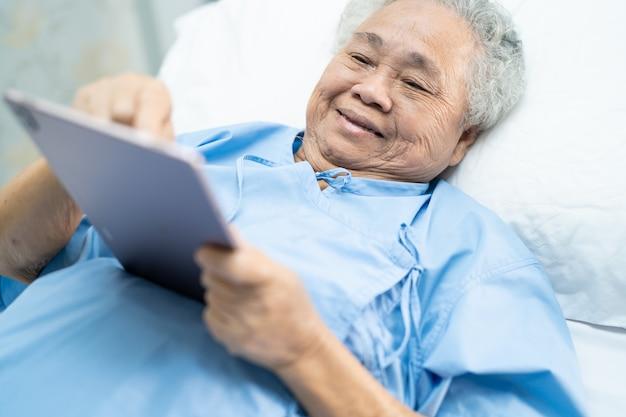 Paciente mujer mayor asiática sosteniendo en sus manos tableta digital