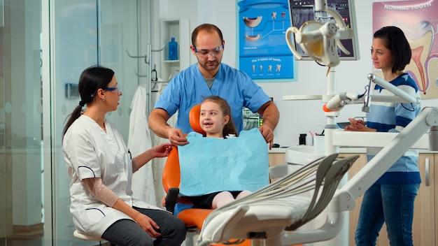 Paciente niña con dolor de dientes que explica el problema dental al dentista pediátrico e indica el dolor de muelas con la lengua. el estomatólogo que toma con la madre sobre el examen estomatológico del niño.