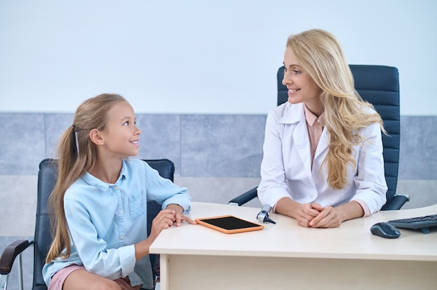 Paciente pediátrico que se comunica con una doctora experimentada de mediana edad