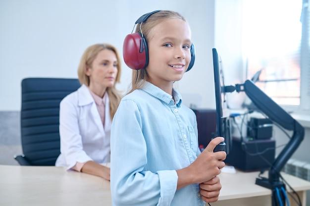 Paciente pediátrico sonriente en auriculares presionando el botón de la respuesta durante la prueba de audiometría realizada por un audiólogo