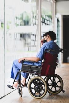 Paciente pensativo sentado en silla de ruedas sintiéndose deprimido y solo.