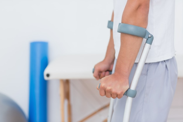 Paciente de pie con muleta en el consultorio médico
