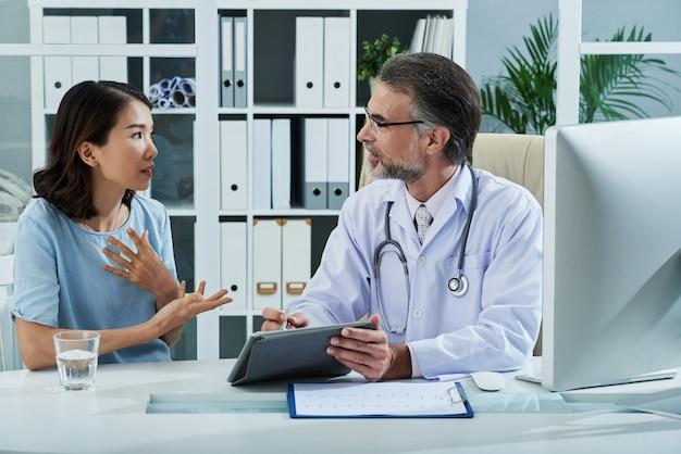 Paciente que le dice al médico acerca de los síntomas de la enfermedad