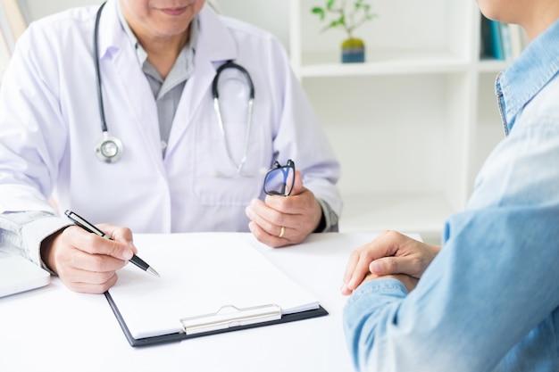 Paciente que escucha atentamente a un doctor de sexo masculino que explica síntomas del paciente o que hace una pregunta mientras que discuten el papeleo juntos en una consulta