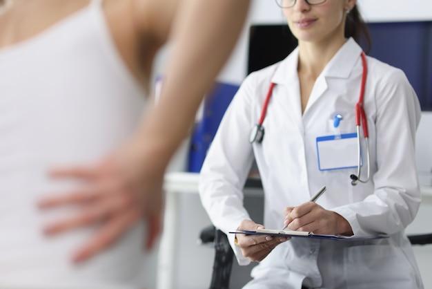 El paciente se queja al médico de dolor de espalda.