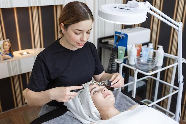 Un paciente recibe un masaje facial eléctrico por cosmetóloga en clínica estética.