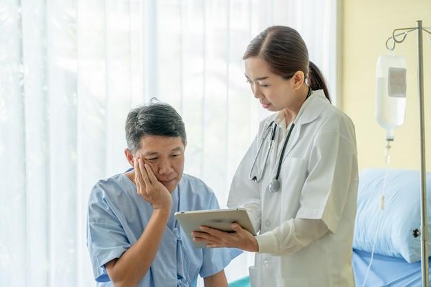 Paciente senior asiático en cama de hospital discutiendo con doctora