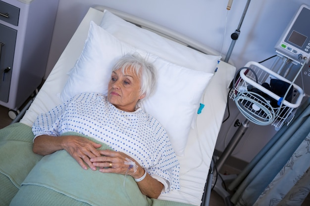 Paciente senior pensativo acostado en la cama