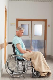 Paciente sentado en una silla de ruedas con una manta
