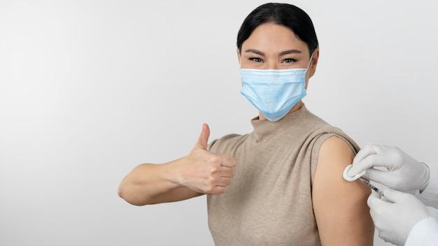 Paciente de sexo femenino con máscara médica mostrando los pulgares hacia arriba mientras recibe la vacuna
