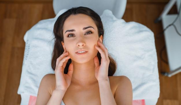 Paciente de sexo femenino en la mesa de tratamiento en la oficina del esteticista, vista superior. procedimiento de rejuvenecimiento en salón de esteticista. cirugía estética contra arrugas, cuidado facial y corporal, terapia de la piel