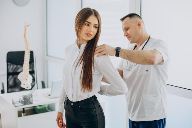 Paciente de sexo femenino que examina la columna vertebral en fisioterapeuta en el centro de vertebrología
