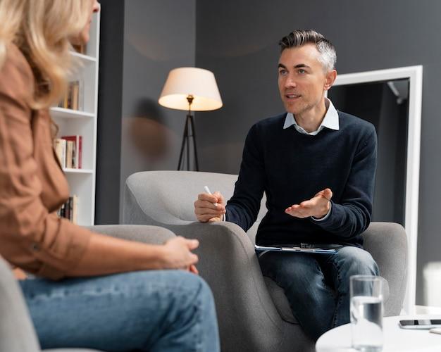 Paciente de tiro medio hablando con el terapeuta de hombre